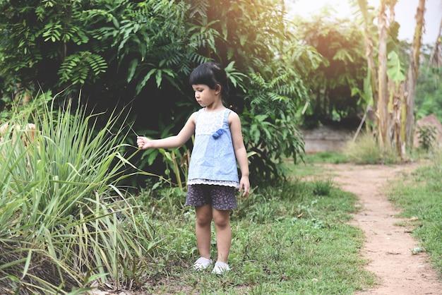 Asiatisches kindermädchen wenig auf naturlandwirtschaftsbauernhof