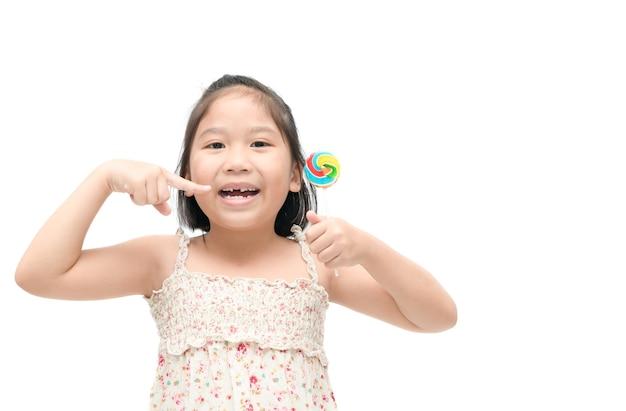Asiatisches kindermädchen zeigen ihren zahn und süßigkeit an hand lokalisiert auf weißem hintergrund, gesundes konzept