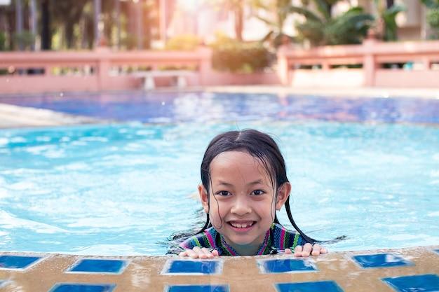 Asiatisches kindermädchenlächeln im swimmingpool