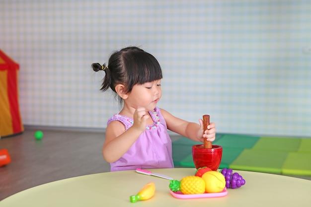 Asiatisches kindermädchenspiel für machen den grünen papayasalat