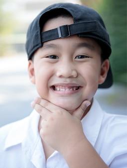 Asiatisches kinderzahnlächelndes gesicht mit glück, das draußen steht