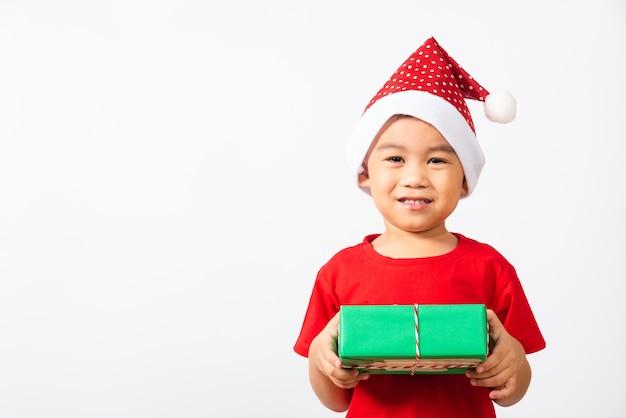 Asiatisches kleines jungenlächeln im roten weihnachtsmann halten geschenkbox auf handkonzept des weihnachtstages