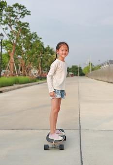 Asiatisches kleines junges mädchen, das ohne schutz auf dem skateboard auf der straße unsicher ist