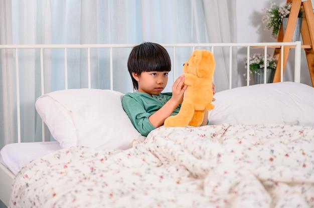 Asiatisches kleines kind allein zu hause und spielt mit puppe. sohn mit spielzeug als freund. einsamer junge unglücklich.
