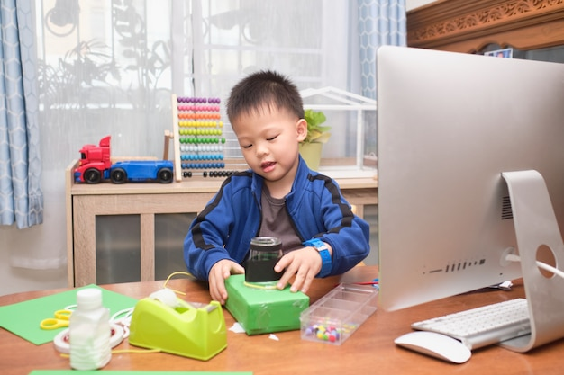 Asiatisches kleines kind, das während seines online-unterrichts zu hause kunst- und bastelprojekte allein mit dem computer macht