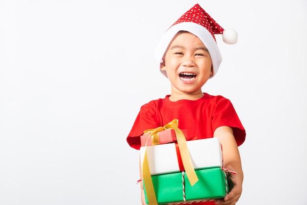 Asiatisches kleines kinderlächeln im roten weihnachtsmann halten geschenkbox auf handkonzept des feiertags weihnachten