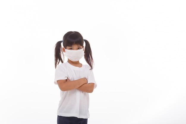 Asiatisches kleines kindermädchen, das atemschutzmaske mit verschränkten armen trägt