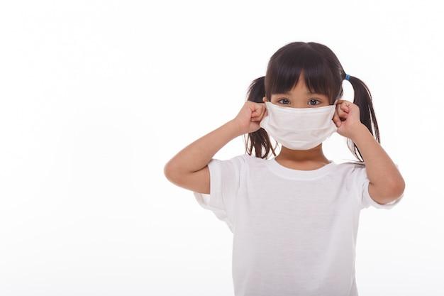 Asiatisches kleines kindermädchen, das atemschutzmaske trägt