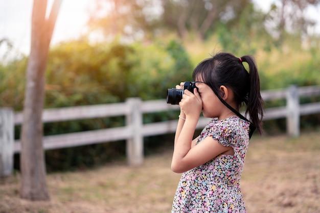 Asiatisches kleines kindermädchen, das filmkamera hält und foto mit grünem natürlichem hintergrund macht