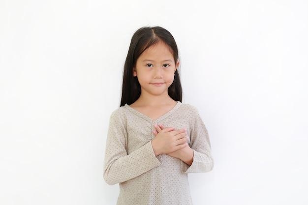 Asiatisches kleines kindermädchen, das hände auf brust lokalisiert auf weißem hintergrund hält