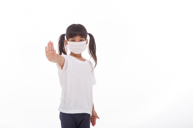 Asiatisches kleines kindermädchen, das maske tut stoppschild tut