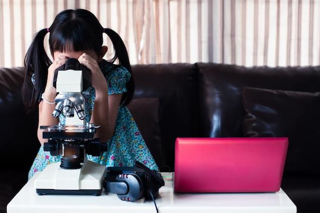 Asiatisches kleines kindermädchen, das mikroskop schaut und online lernt, indem es laptop und zu hause fernunterricht verwendet
