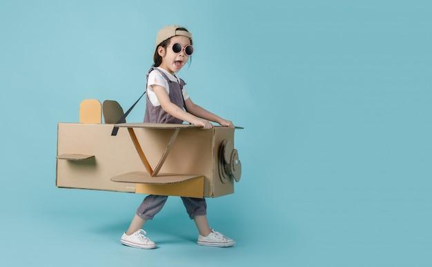 Asiatisches kleines kindermädchen, das mit pappspielzeugflugzeug spielt