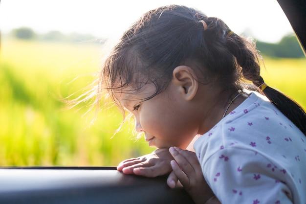 Asiatisches kleines kindermädchen, das spaß lächelt und hat, mit dem auto zu reisen und heraus vom autofenster zu schauen