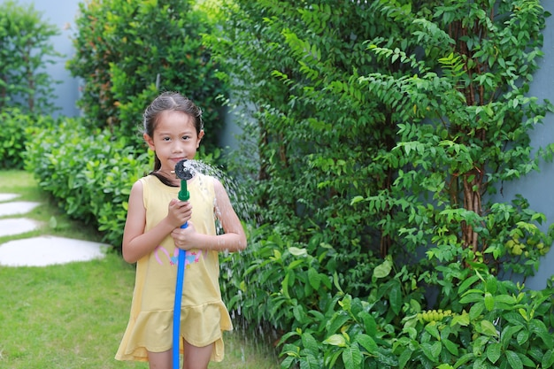 Asiatisches kleines kindermädchen, das wasserspray auf bäume gießt