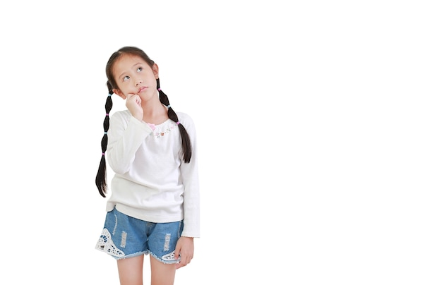 Asiatisches kleines kindermädchen mit denkendem ausdruck und nach oben lokalisiert auf weißem hintergrund. kind, das versucht, eine lösung zu finden, gestikuliert.