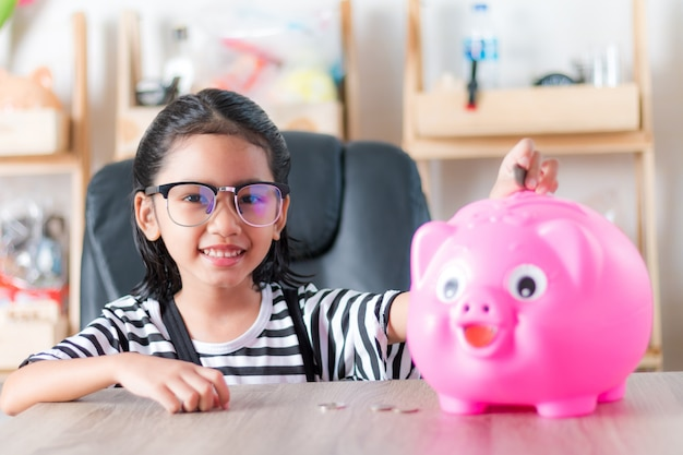 Asiatisches kleines mädchen beim einlegen der münze in die flache schärfentiefe des sparschweins wählen fokus im gesicht
