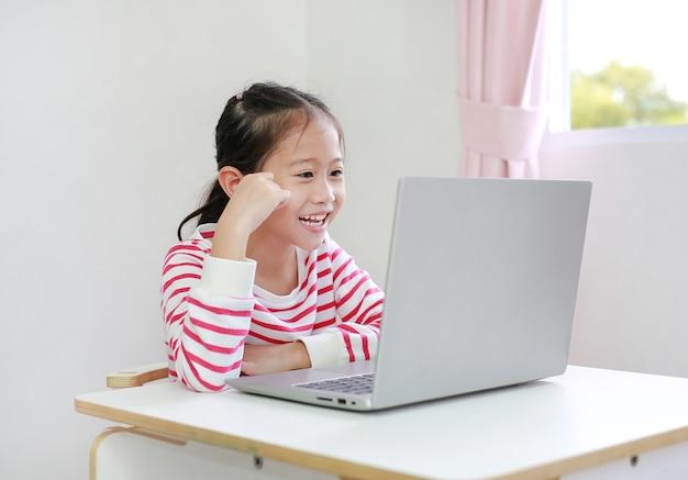 Asiatisches kleines mädchen, das am schreibtisch sitzt, genießt, karikatur auf laptop zu hause zu beobachten
