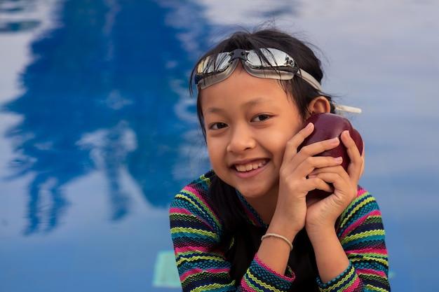 Asiatisches kleines mädchen, das apfel am schwimmbad mit tragender schwimmbrille hält