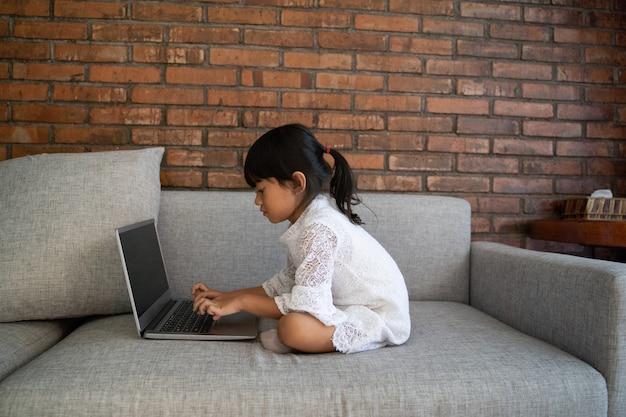 Asiatisches kleines mädchen, das auf der couch sitzt, die spaß mit laptop hat