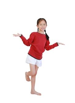 Asiatisches kleines mädchen, das auf einem bein steht und die handbewegung lokalisiert auf weißem hintergrund mit beschneidungspfad öffnet. in voller länge