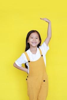 Asiatisches kleines mädchen, das auf gelbem hintergrund glücklich ist