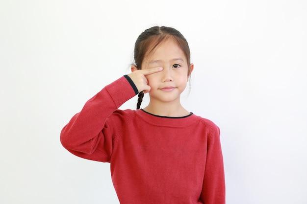 Asiatisches kleines mädchen, das ein auge durch zeigefinger schließt