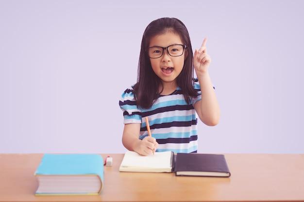 Asiatisches kleines mädchen, das ein buch auf tisch schreibt. zeigefinger oben mit offenem mund, isoliert auf grauem hintergrund