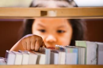 Asiatisches kleines mädchen, das ein buch in der bibliothek wählt. vintage-farbton