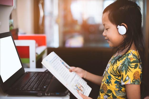 Asiatisches kleines mädchen, das ein buch mit suchdaten durch notizbuch liest.