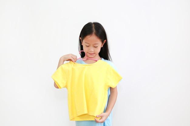 Asiatisches kleines mädchen, das ein gelbes hemd auf weiß versucht