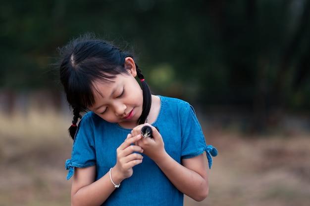 Asiatisches kleines mädchen, das ein küken in ihrer hand hält