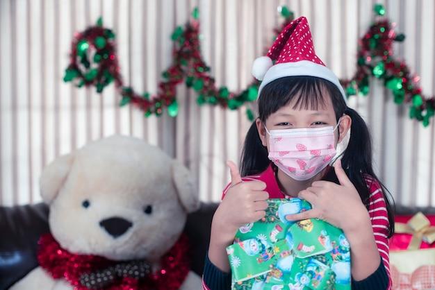Asiatisches kleines mädchen, das eine geschenkbox mit verschleißgesichtsmaske am weihnachtstag hält