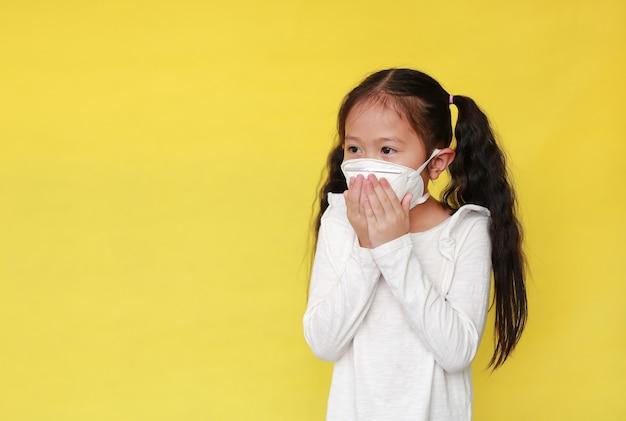 Asiatisches kleines mädchen, das eine schutzmaske trägt