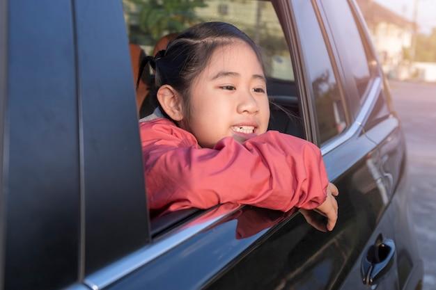 Asiatisches kleines mädchen, das etwas aus dem auto schaut.