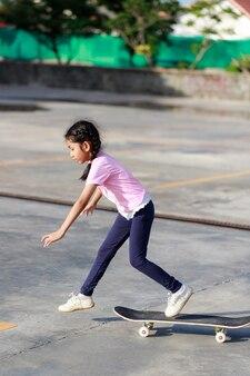 Asiatisches kleines mädchen, das flache schärfentiefe des ausgewählten fokus des skateboards spielt