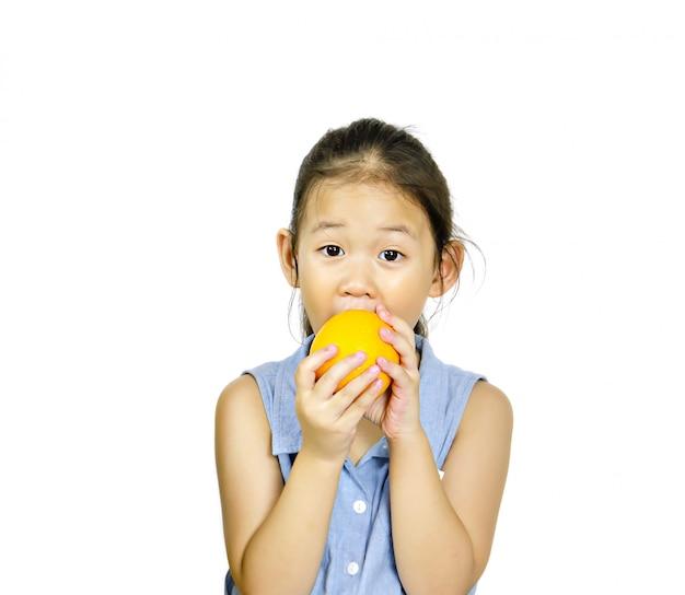 Asiatisches kleines mädchen, das frische orange anhält