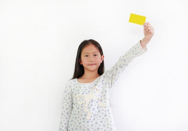 Asiatisches kleines mädchen, das gelbe karte auf weißem hintergrund hält