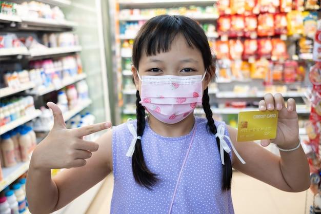 Asiatisches kleines mädchen, das gesichtsmaske trägt und mit showkreditkarte steht