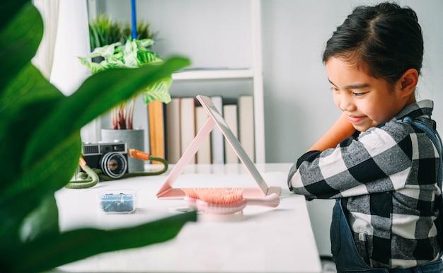 Asiatisches kleines mädchen, das haar kämmt. lächelnde dame im mirrorcombing-haar. baby-maskenbildner. kinderfriseur