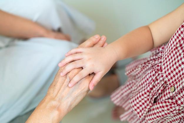 Asiatisches kleines mädchen, das ihre großmutterhand mit sorgfalt und liebe emotional hält