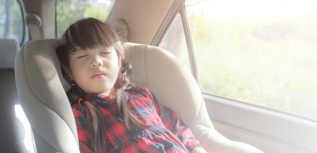 Asiatisches kleines mädchen, das im auto mit autositz schläft