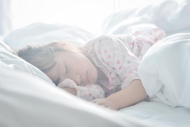 Asiatisches kleines mädchen, das im bett auf der morgenzeit mit sonnenaufganglichtweichzeichnung schläft