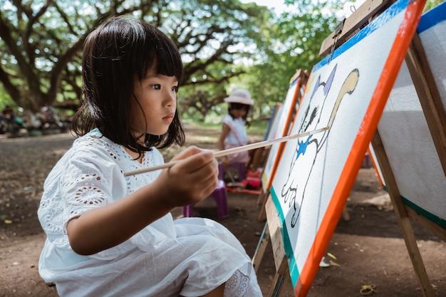Asiatisches kleines mädchen, das im garten zeichnet