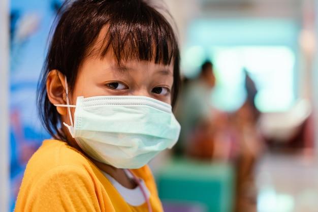 Asiatisches kleines mädchen, das in einem krankenhaus sitzt und medizinische maske mit traurigen augen und hoffnung trägt