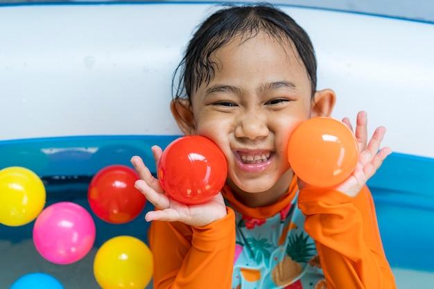 Asiatisches kleines mädchen, das in einem pool spielt