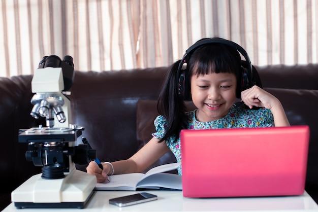 Asiatisches kleines mädchen, das kopfhörer trägt, die online lernen, indem sie laptop und mikroskop zu hause, fernunterricht verwenden