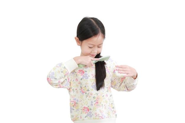 Asiatisches kleines mädchen, das langes haar auf weiß kämmt
