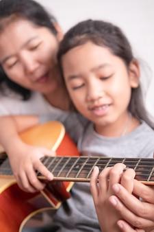 Asiatisches kleines mädchen, das lernt, musik mit glück zu spielen