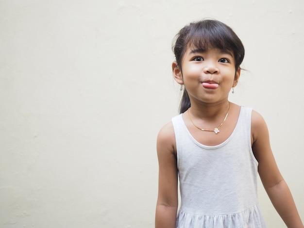 Asiatisches kleines mädchen, das lustigen gesichtsausdruck macht